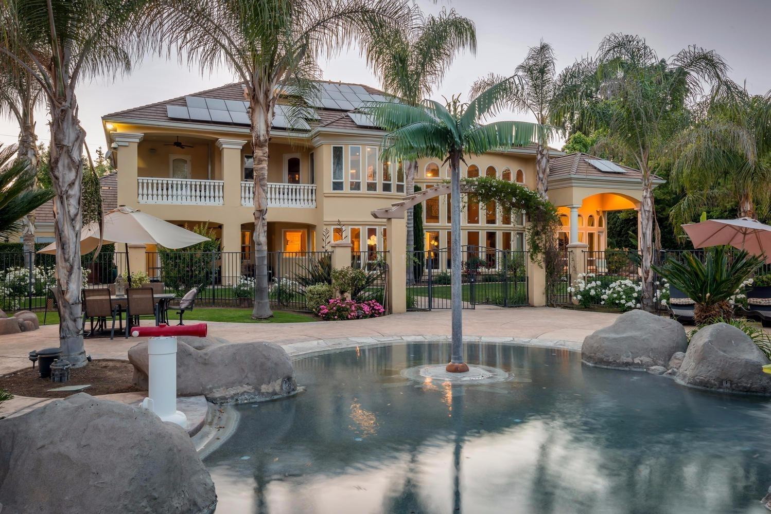 pros & cons of selling your home during the holidays - mansion and pool at dusk with palm trees, serene